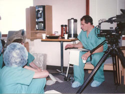 Man in scrubs next to video camera talking to people